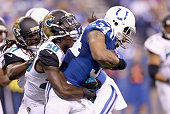 Trent Richardson of the Indianapolis Colts runs with the ball while tackled by Telvin Smith of the Jacksonville Jaguars during the game at Lucas Oil...