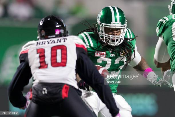 Trent Richardson of the Saskatchewan Roughriders looks to avoid Serderius Bryant of the Ottawa Redblacks during a run in the first of the game...