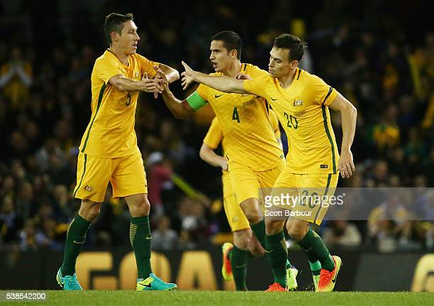 Trent Sainsbury of Australia is congratulated by Mark Milligan and Tim Cahill after kicking a goal during the International Friendly match between...