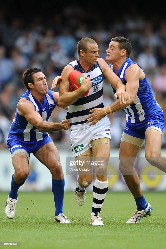Trent West of the Cats is tackled by <a gi-track='captionPersonalityLinkClicked' href=/galleries/search?phrase=Michael+Firrito&family=editorial&specificpeople=221362 ng-click='$event.stopPropagation()'>Michael Firrito</a> and Nathan Grima (R) during the round two AFL match between the Geelong Cats and the North Melbourne Kangaroos at Etihad Stadium on April 7, 2013 in Melbourne, Australia.