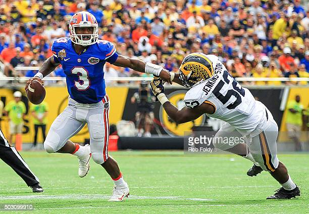 Treon Harris of the Florida Gators in action against Royce JenkinsStone of the Michigan Wolverines during the first half of the Buffalo Wild Wings...