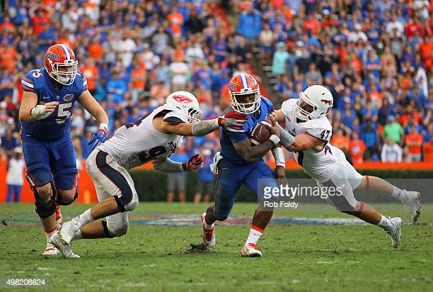 Treon Harris of the Florida Gators is stopped by Hunter Snyder and Jerrad Ward of the Florida Atlantic Owls during the second half of the game at Ben...