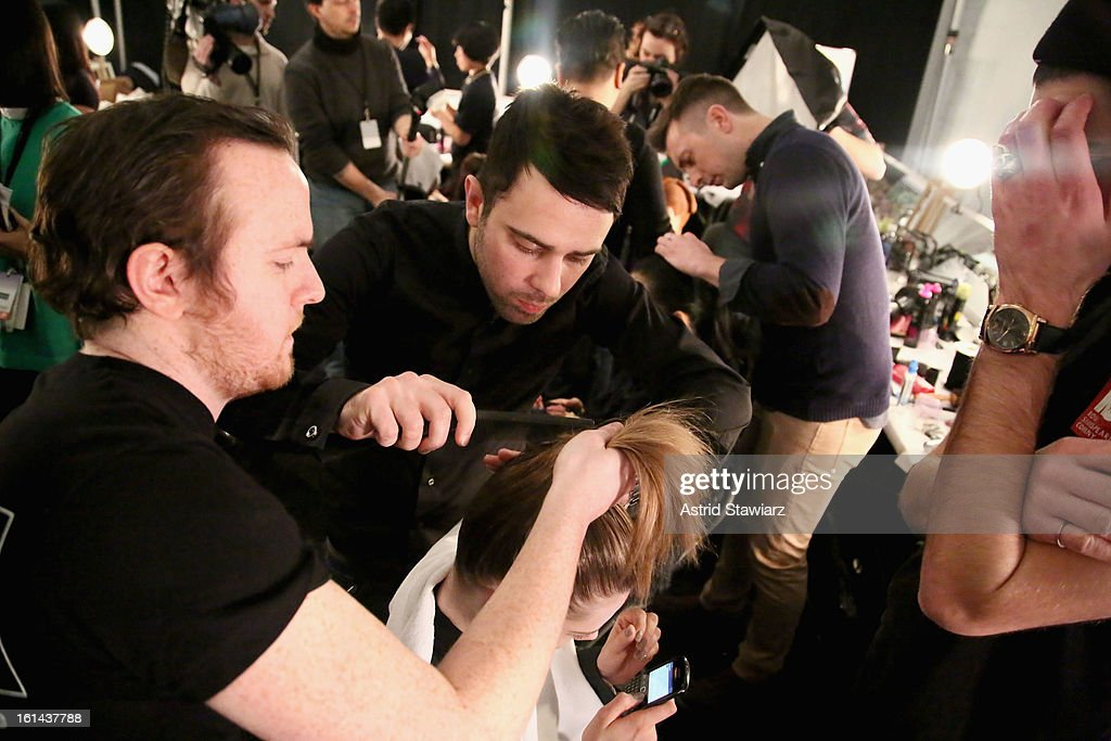 TRESemme hair stylist Matthew Curtis(C) prepares a model backstage at the Vivienne Tam Fall 2013 fashion show with TRESemme during Mercedes-Benz Fashion Week at The Stage at Lincoln Center on February 10, 2013 in New York City.