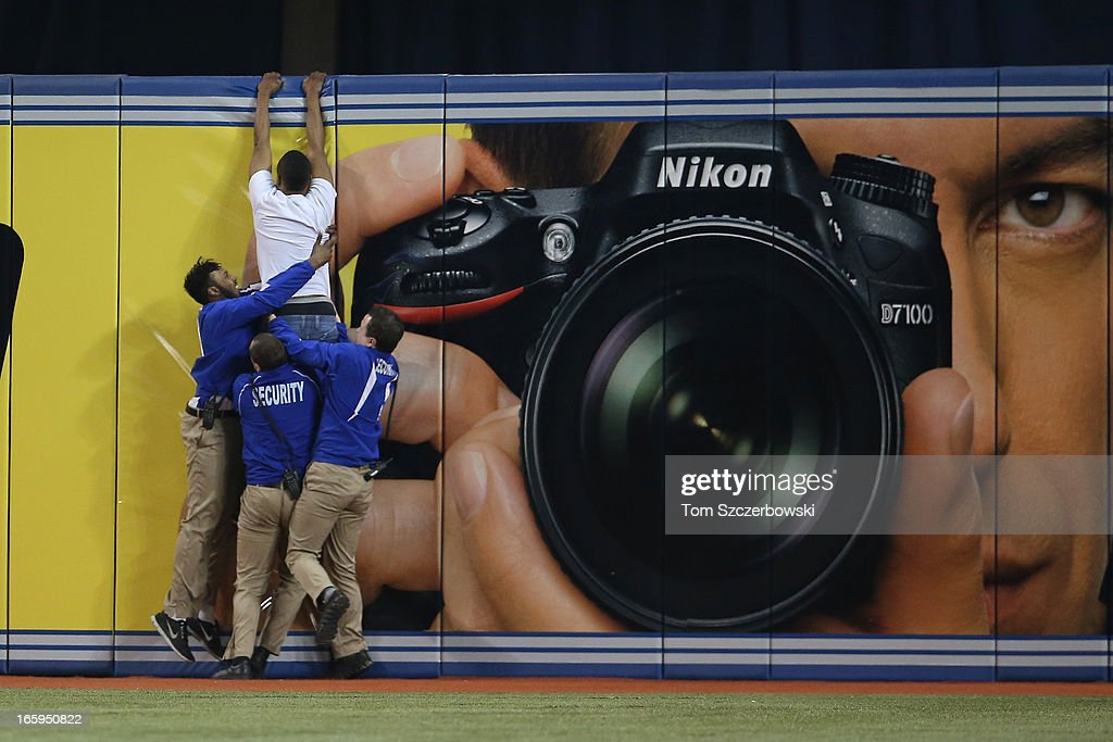 A trespasser tries to jump the outfield wall as security guards pull him down during the Toronto Blue Jays MLB game against the Boston Red Sox on April 7, 2013 at Rogers Centre in Toronto, Ontario, Canada.