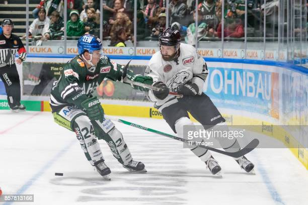 J Trevelyan of Augsburger Panther and Josef Lala of Nuernberg Ice Tigers battle for the ball during the DEL match between Augsburger Panther and ERC...