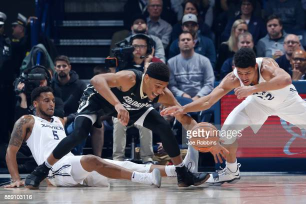Trevon Bluiett and Kaiser Gates of the Xavier Musketeers battle for a loose ball against George King of the Colorado Buffaloes in the first half of a...