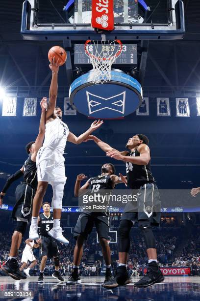 Trevon Bluiett of the Xavier Musketeers drives to the basket against George King and Namon Wright of the Colorado Buffaloes in the first half of a...