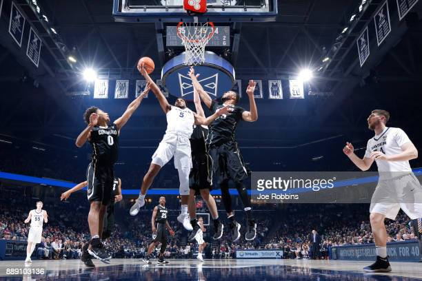 Trevon Bluiett of the Xavier Musketeers drives to the basket against D'Shawn Schwartz and Dallas Walton of the Colorado Buffaloes in the first half...