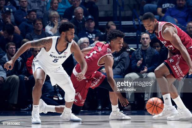Trevon Bluiett of the Xavier Musketeers knocks the ball away from Tyrei Randall of the Rider Broncs in the first half of a game at Cintas Center on...