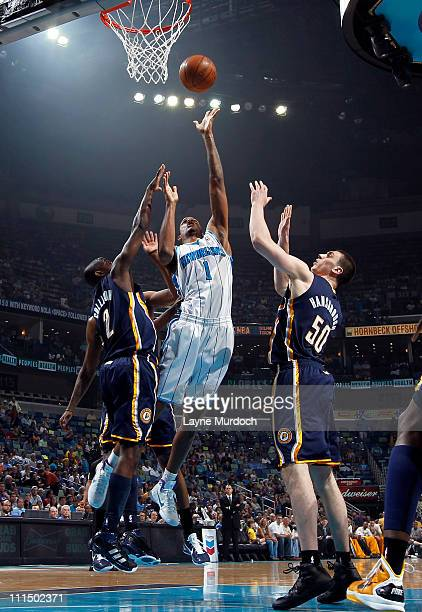 Trevor Ariza of the New Orleans Hornets shoots against Darren Collison and Tyler Hansbrough of the Indiana Pacers on April 3 2011 at the New Orleans...