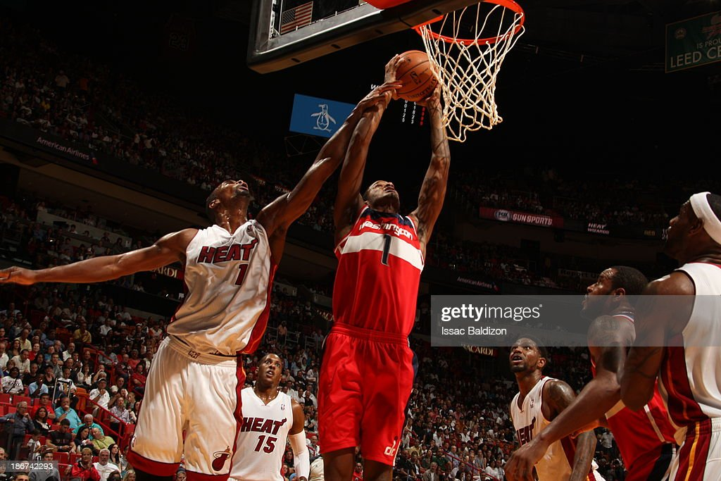 Trevor Ariza #1 of the Washington Wizards dunks against Chris Bosh #1 of the Miami Heat on November 3, 2013 at American Airlines Arena in Miami, Florida.