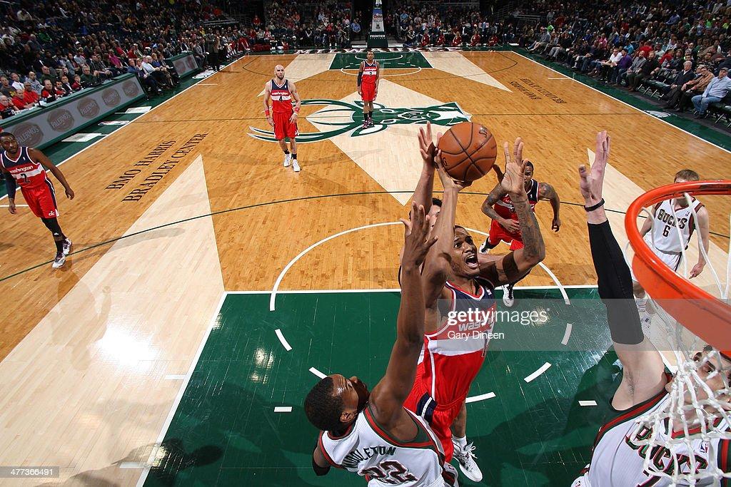 Trevor Ariza #1 of the Washington Wizards shoots against (L-R) Khris Middleton #22 and Ersan Ilyasova #7 of the Milwaukee Bucks on March 8, 2014 at the BMO Harris Bradley Center in Milwaukee, Wisconsin.