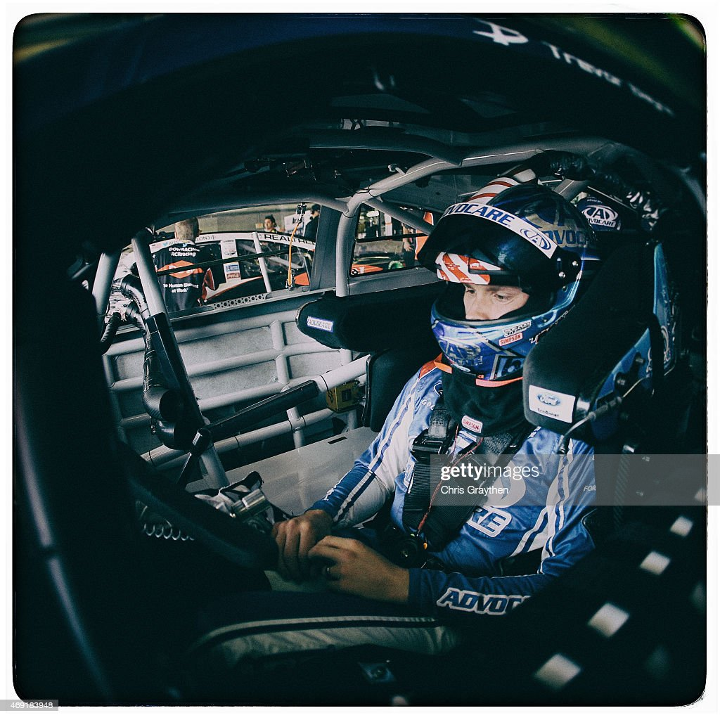 Trevor Bayne driver of the AdvoCare Ford sits in his car in the garage area during practice for the NASCAR Sprint Cup Series Duck Commander 500 at...