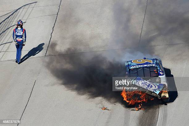 Trevor Bayne driver of the AdvoCare Ford stands near his car after crashing during the NASCAR Nationwide Series O'Reilly Auto Parts Challenge at...