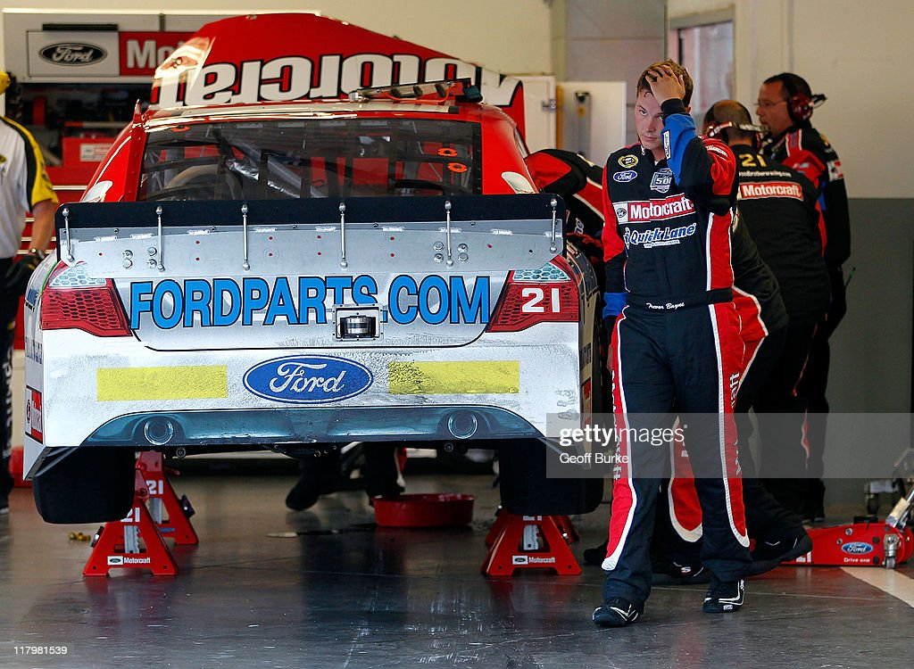 Trevor Bayne driver of the Motorcraft/Quick Lane Tire Auto Center Ford walks through the garage as his crew works on his car after he wrecked early...