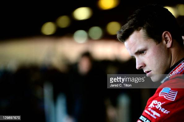 Trevor Bayne driver of the Motorcraft/Quick Lane Tire Auto Center Ford stands in the garage area during practice for the NASCAR Sprint Cup Series...