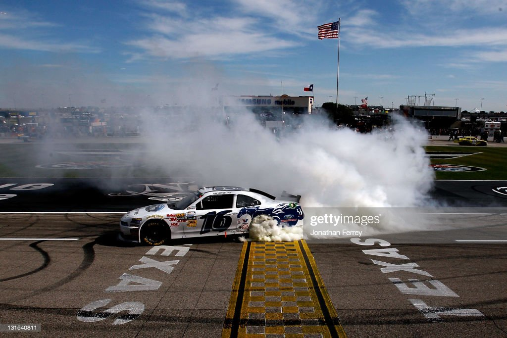 Trevor Bayne driver of the RickyVsTrevorcom Ford celebrates with a burnout after winning the NASCAR Nationwide Series O'Reilly Auto Parts Challenge...