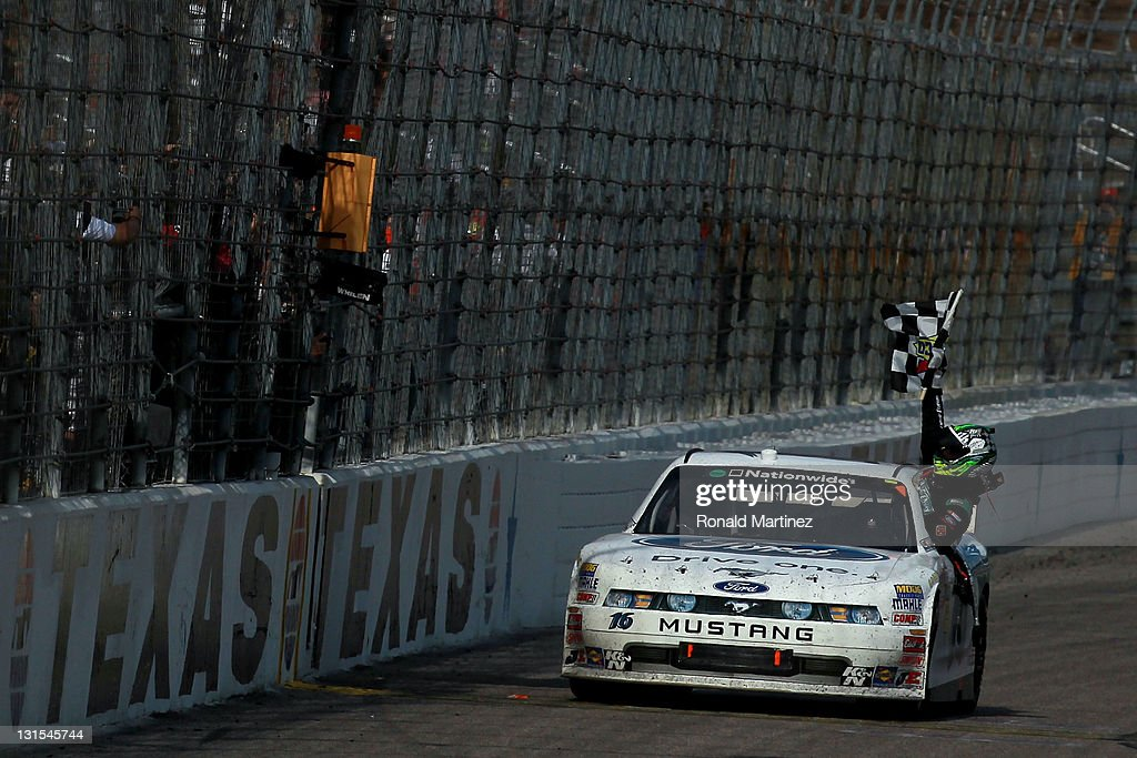 Trevor Bayne driver of the RickyVsTrevorcom Ford celebrates with the Sunoco checkered flag after he won the NASCAR Nationwide Series O'Reilly Auto...