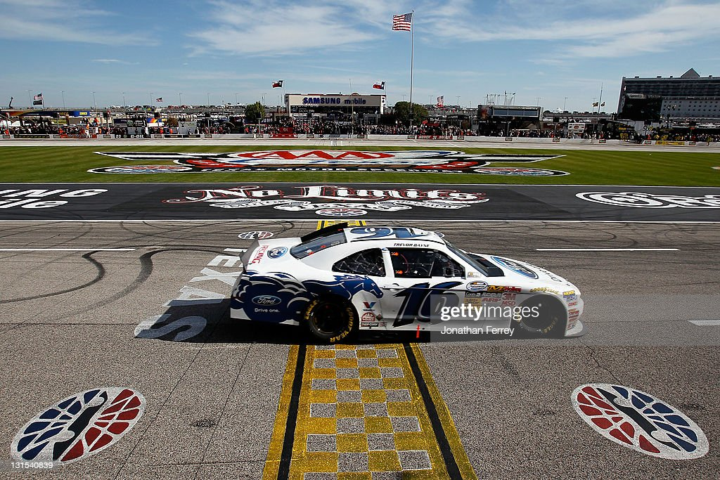 Trevor Bayne driver of the RickyVsTrevorcom Ford crosses the finish line to win the NASCAR Nationwide Series O'Reilly Auto Parts Challenge at Texas...