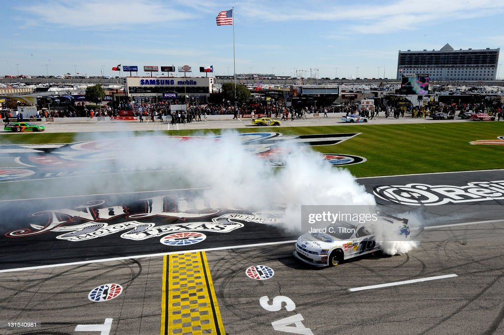 Trevor Bayne driver of the RickyVsTrevorcom Ford performs a burnout in celebration of winning the NASCAR Nationwide Series O'Reilly Auto Parts...