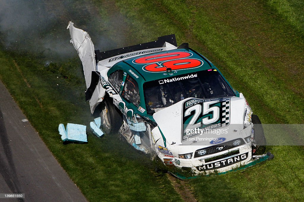 <a gi-track='captionPersonalityLinkClicked' href=/galleries/search?phrase=Trevor+Bayne&family=editorial&specificpeople=5533943 ng-click='$event.stopPropagation()'>Trevor Bayne</a> drives the wrecked #60 Roush Fenway Racing Ford through the grass after being involved in a last lap on track incident during the NASCAR Nationwide Series DRIVE4COPD 300 at Daytona International Speedway on February 25, 2012 in Daytona Beach, Florida.