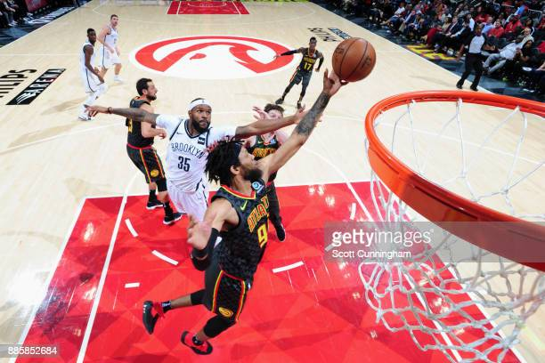 Trevor Booker of the Brooklyn Nets and DeAndre' Bembry of the Atlanta Hawks jump for the rebound on December 4 2017 at Philips Arena in Atlanta...