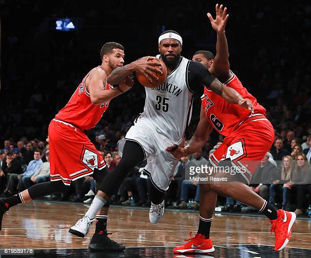 Trevor Booker of the Brooklyn Nets drives to the basket past Michael CarterWilliams and Cristiano Felicio of the Chicago Bulls during the first half...