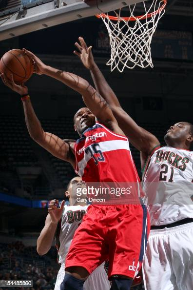 Trevor Booker of the Washington Wizards shoots against Tobias Harris and Samuel Dalembert of the Milwaukee Bucks during the NBA preseason game on...