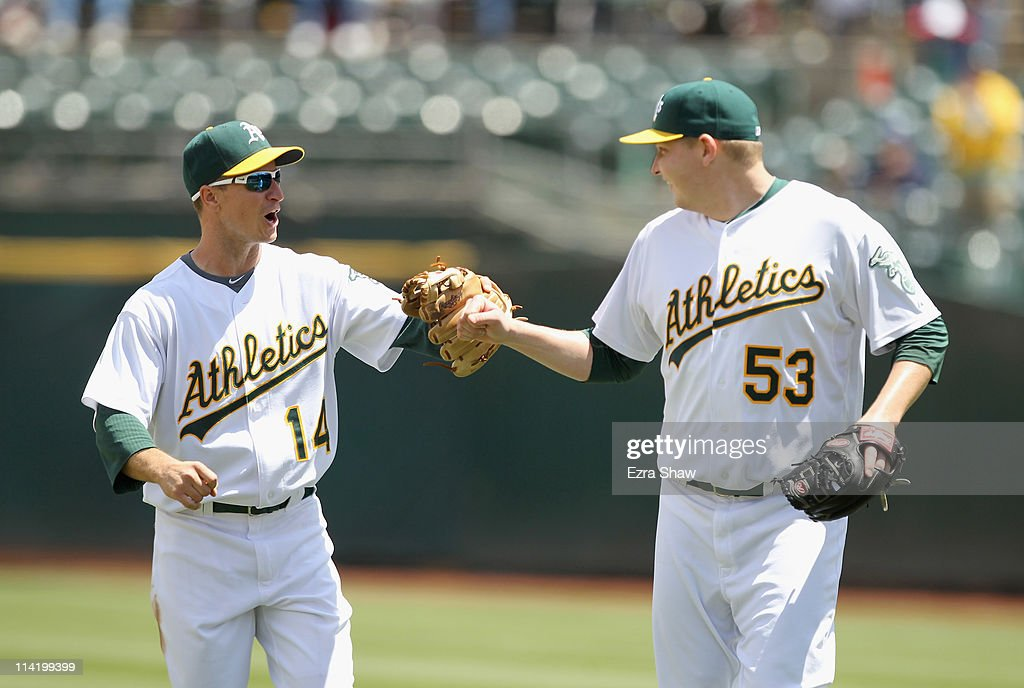 Trevor Cahill #53 congratulates Mark Ellis #14 of the Oakland Athletics after he turned a double play that ended the third inning against the Chicago White Sox at Oakland-Alameda County Coliseum on May 15, 2011 in Oakland, California.