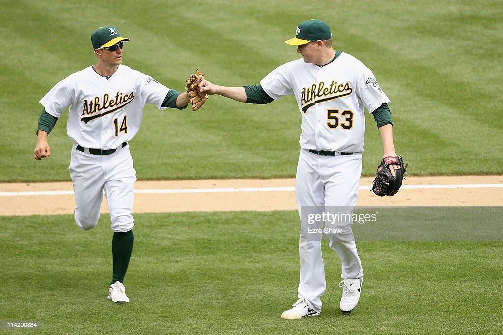 Trevor Cahill #53 of the Oakland Athletics congratulates Mark Ellis #14 of the Oakland Athletics after he made a play to end the seventh inning against the Chicago White Sox at Oakland-Alameda County Coliseum on May 15, 2011 in Oakland, California.