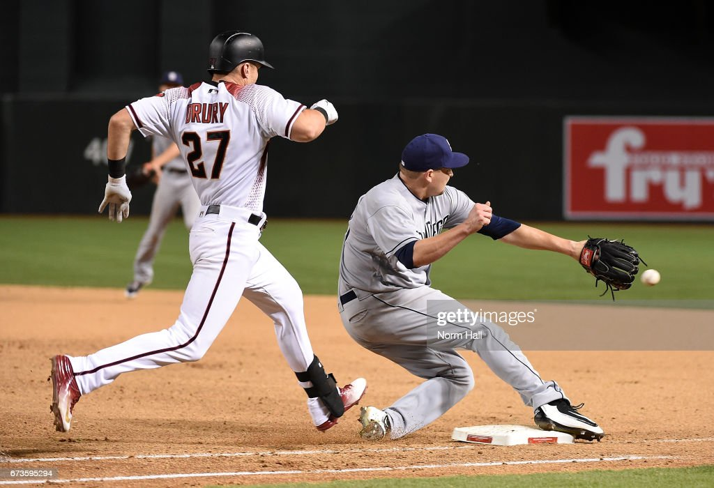 Trevor Cahill #38 of the San Diego Padres attempts to cover first base and catch a throw from Wil Myers #4 as Brandon Drury #27 of the Arizona Diamondbacks runs up the baseline during the fifth inning at Chase Field on April 26, 2017 in Phoenix, Arizona. Drury was safe at first base.