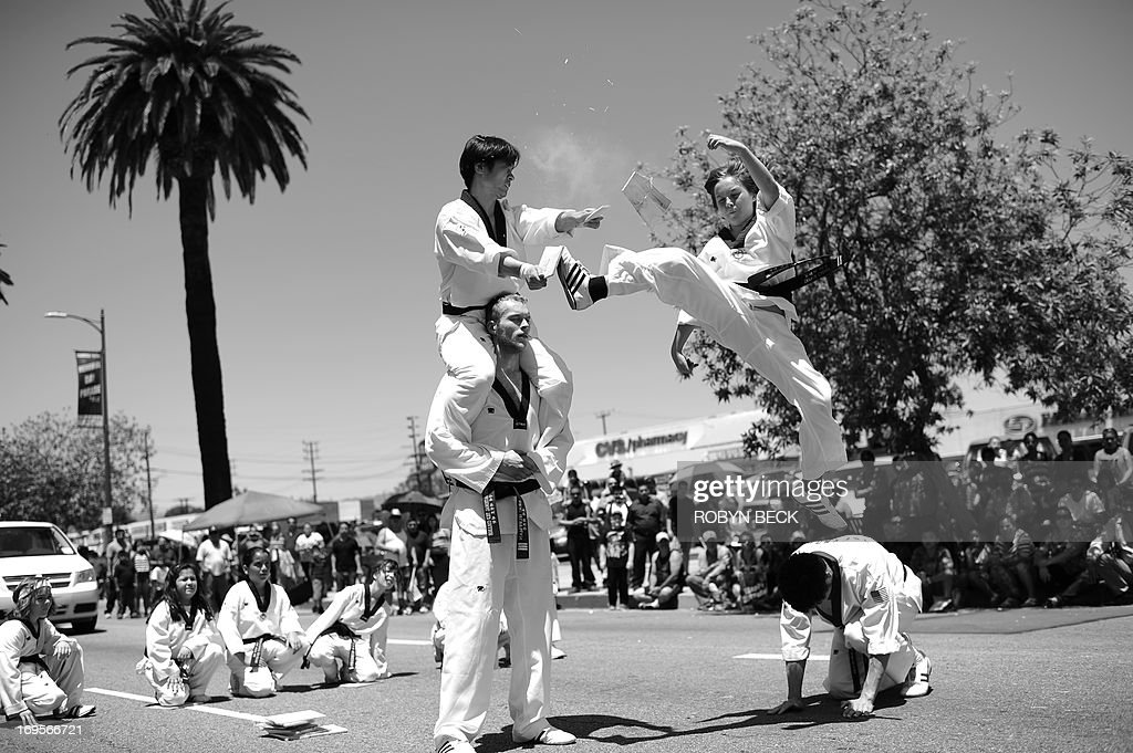 Trevor Carson (top right) of the International Taekwando College breaks a wood board with his foot as he marches with his school in the 2013 Canoga Park Memorial Day Parade in Canoga Park, California, May 27, 2013. Canoga Park is located in the northwestern corner of the San Fernando Valley aproximately 27 miles (44km) northwest of downtown Los Angeles. Memorial Day is a day of remembering the men and women who died while serving in the United States Armed Forces. AFP PHOTO / ROBYN BECK