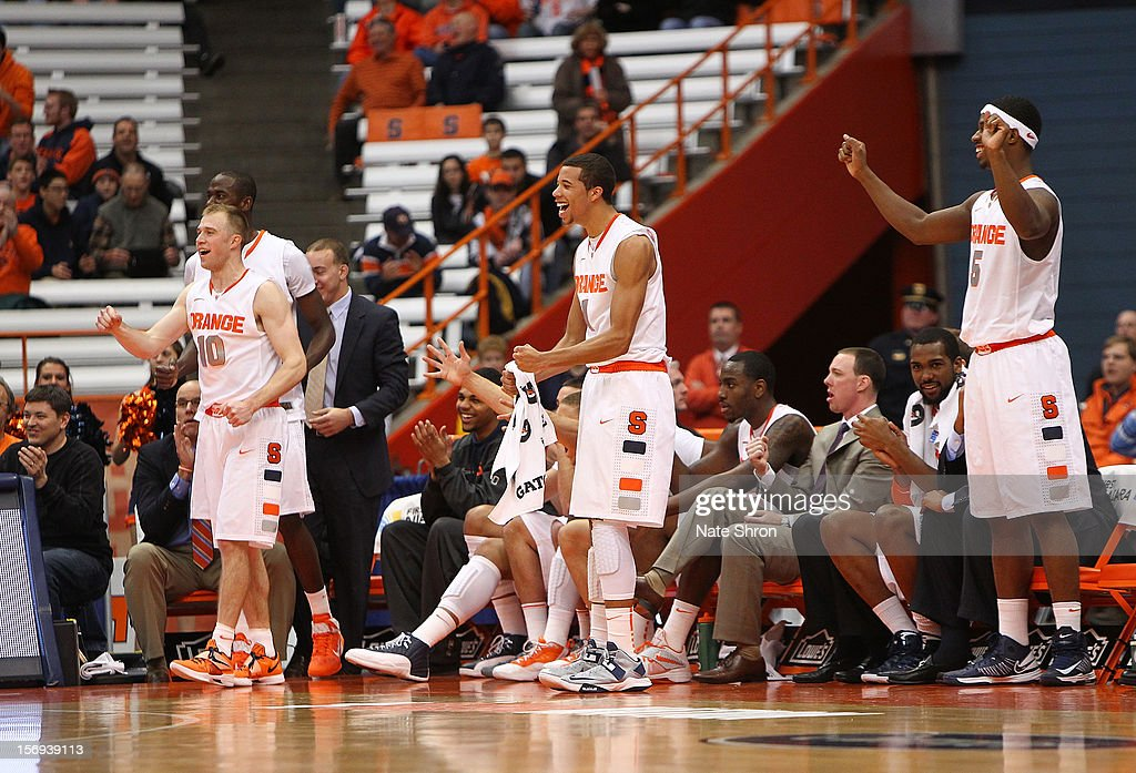 Trevor Cooney #10, Michael Carter-Williams #1 and C.J. Fair #5 of the Syracuse Orange stand and chair on the sideline during the win over the Colgate Raiders at the Carrier Dome on November 25, 2012 in Syracuse, New York.
