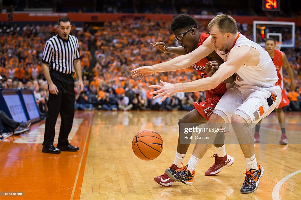 Trevor Cooney #10 of Syracuse Orange comes up with a loose ball over Robert Hatter #5 of Cornell Big Red during the second half on November 8, 2013 at the Carrier Dome in Syracuse, New York.