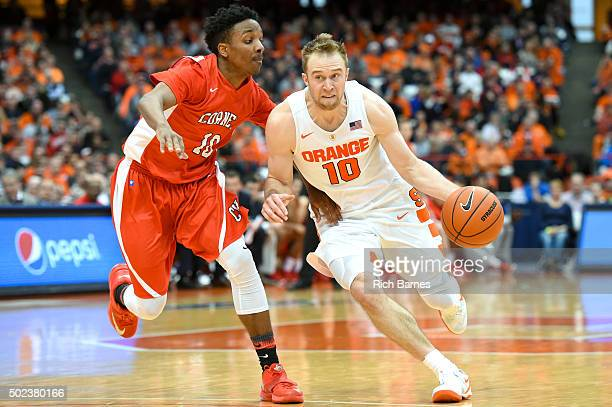 Trevor Cooney of the Syracuse Orange drives to the basket against the defense of Matt Morgan of the Cornell Big Red during the second half at the...