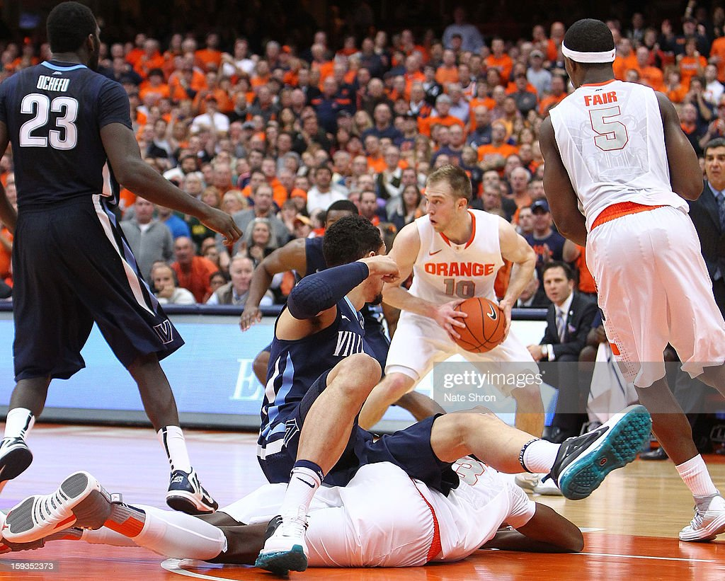 Trevor Cooney #10 of the Syracuse Orange holds the ball as Maurice Sutton #25 of the Villanova Wildcats falls over Jerami Grant #3 as C.J. Fair #5 and Daniel Ochefu #23 look on during the game at the Carrier Dome on January 12, 2013 in Syracuse, New York.