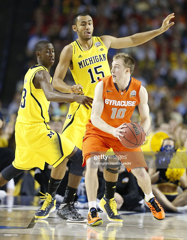 Trevor Cooney (10) of the Syracuse Orange looked to pass as Caris LeVert (23) and Jon Horford (15) of the Michigan Wolverines applied pressure in first-half action in an NCAA Final Four semifinal at the Georgia Dome in Atlanta, Georgia, Saturday, April 6, 2013.