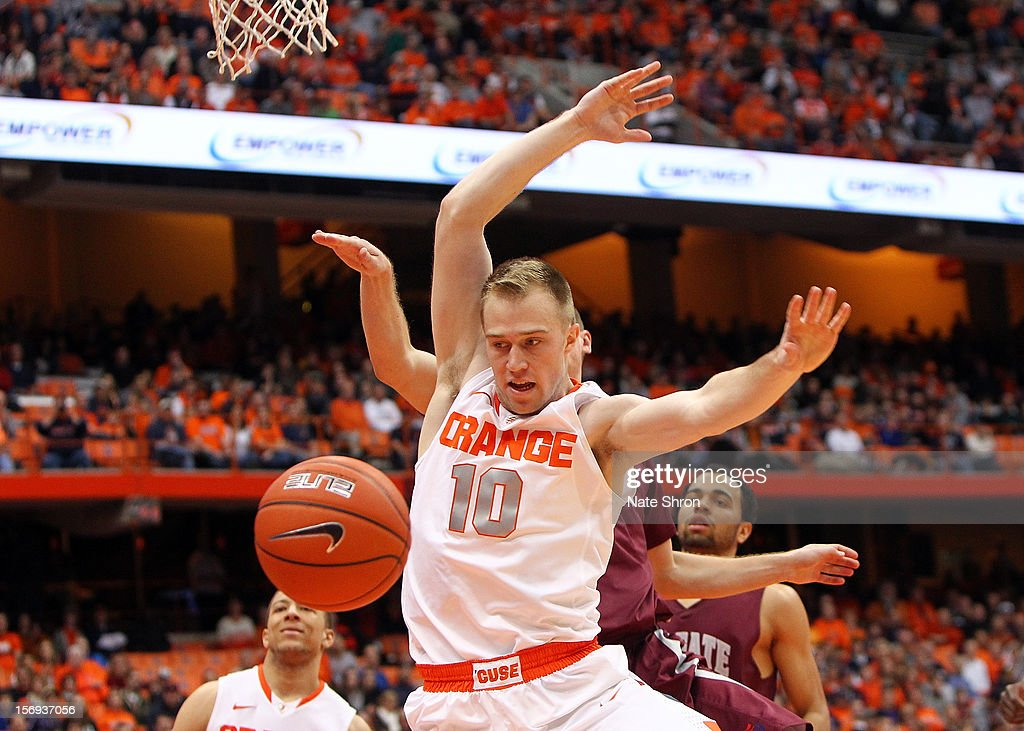 Trevor Cooney #10 of the Syracuse Orange loses the ball as he drives to the basket against Pat Moore #5 and Damon Sherman-Newsome #21 of the Colgate Raiders during the game at the Carrier Dome on November 25, 2012 in Syracuse, New York.