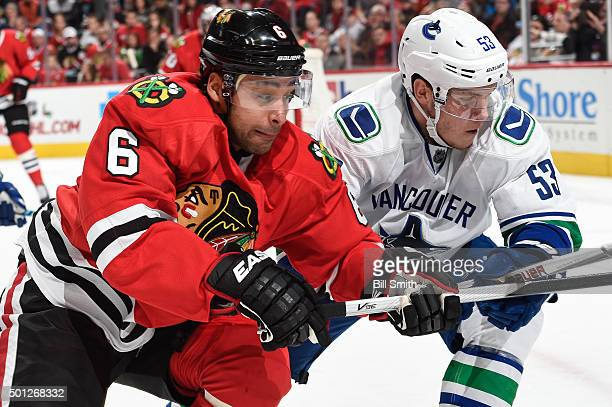 Trevor Daley of the Chicago Blackhawks and Bo Horvat of the Vancouver Canucks watch for the puck during the NHL game at the United Center on December...