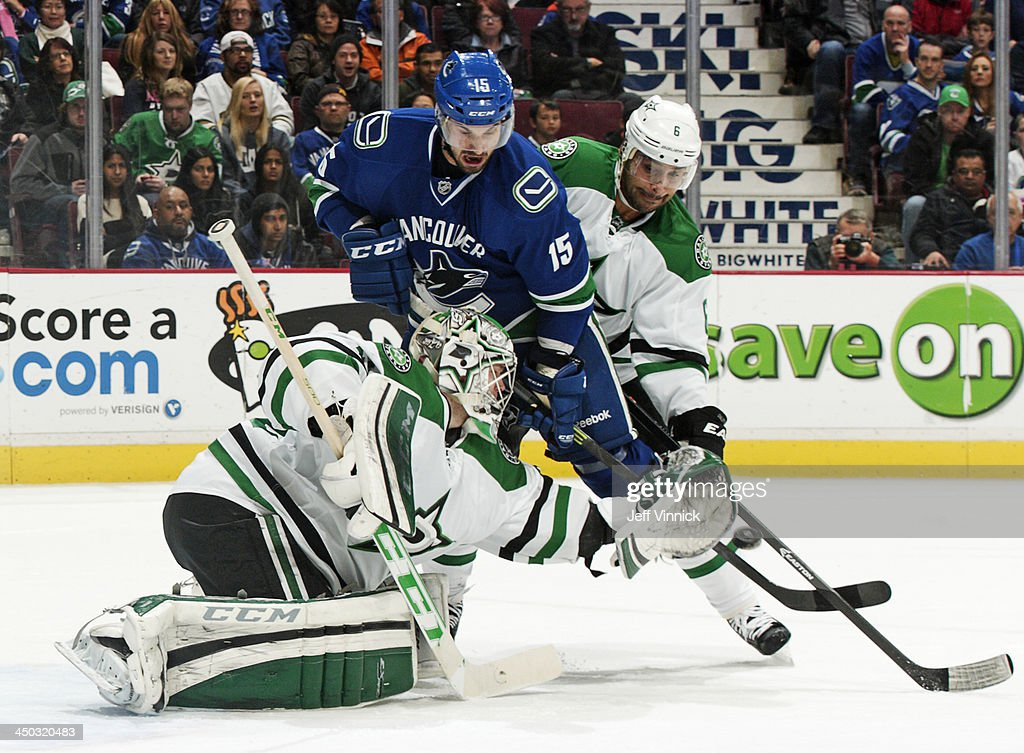 Trevor Daley #6 of the Dallas Stars checks Brad Richardson #15 of the Vancouver Canucks while Kari Lehtonen #32 of the Stars makes a save during their NHL game at Rogers Arena on November 17, 2013 in Vancouver, British Columbia, Canada. Dallas won 2-1.