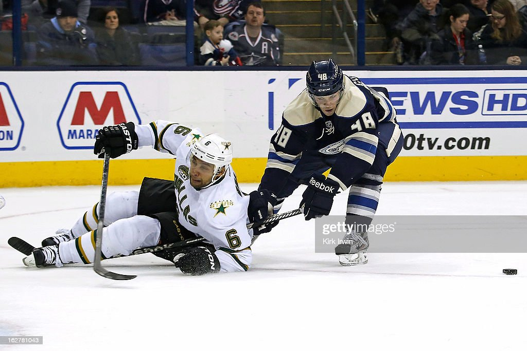 Trevor Daley #6 of the Dallas Stars is knocked down by Cody Goloubef #48 of the Columbus Blue Jackets while attempting to shoot the puck during the overtime period on February 26, 2013 at Nationwide Arena in Columbus, Ohio. Dallas defeated Columbus 5-4 in overtime.