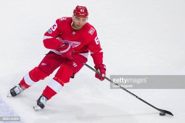 Trevor Daley of the Detroit Red Wings skates up ice with the puck against the Minnesota Wild during the first ever NHL game at the new Little Caesars...