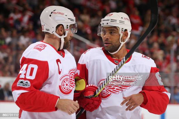 Trevor Daley of the Detroit Red Wings talks with Henrik Zetterberg during a break from the second period of the NHL game against the Arizona Coyotes...