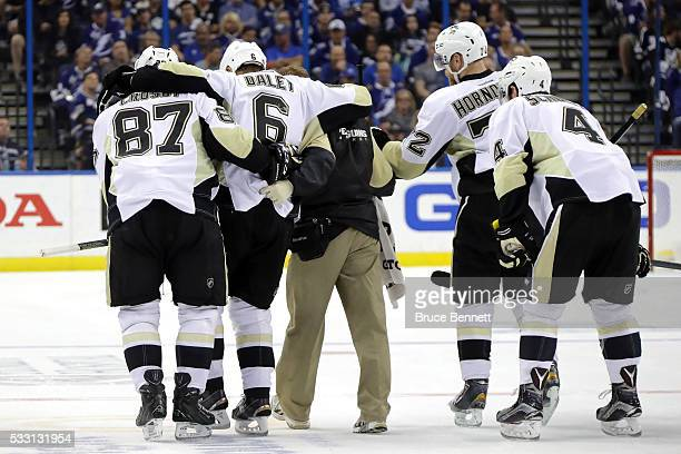 Trevor Daley of the Pittsburgh Penguins gets helped off the ice after being injured during the second period against the Tampa Bay Lightningin Game...