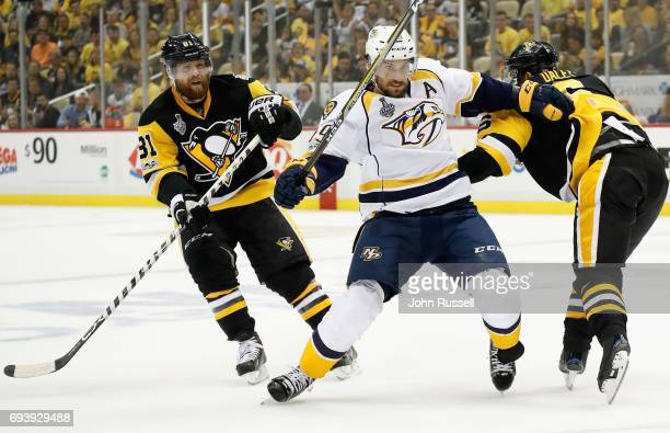 Trevor Daley of the Pittsburgh Penguins grabs Roman Josi of the Nashville Predators in front of Phil Kessel during the first period of Game Five of...