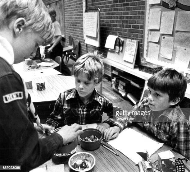 Trevor Dutton above left buys a pet rock from from Brad Rutledge and Matt Beeter as Mark Twain Elementary School students marketed their firms'...