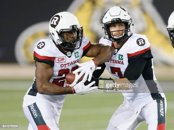 Trevor Harris hands the ball off to William Powell of the Ottawa Redblacks during a CFL game against the Hamilton TigerCats at Tim Hortons Field on...