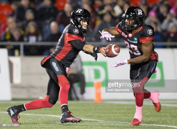 Trevor Harris of the Ottawa Redblacks hands the ball off to Mossis Madu Jr against the Hamilton TigerCats in Canadian Football League play at TD...