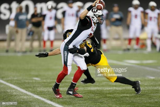 Trevor Harris of the Ottawa Redblacks tries to avoid a tackle by Justin Capicciotti of the Hamilton TigerCats during a CFL game at Tim Hortons Field...