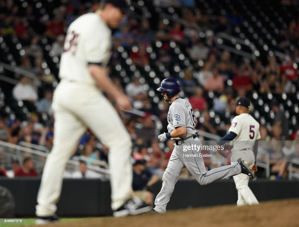 Trevor Hildenberger #39 and Eduardo Escobar #5 of the Minnesota Twins look on as Austin Hedges #18 of the San Diego Padres rounds the bases after hitting a solo home run during the eighth inning of the game on September 13, 2017 at Target Field in Minneapolis, Minnesota. The Twins defeated the Padres 3-1 in ten innings.